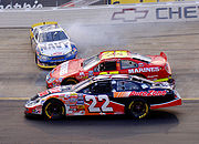 Mark McFarland (88) spins at Bristol Motor Speedway, while Kenny Wallace (22) and Ashton Lewis Jr. (25) pass to the inside