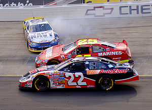 Criticism of NASCAR - Mark McFarland (88) spins at Bristol Motor Speedway, while Kenny Wallace (22) and Ashton Lewis Jr. (25) pass to the inside during a Busch Series event.