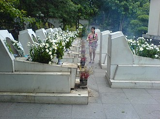 Cemetery for ten unmarried girls who volunteered for logistical activities, who died in a B-52 raid at Dong Loc Junction, a strategic junction along the Ho Chi Minh trail Lighting incense at the Dong Loc Junction memorial.jpg