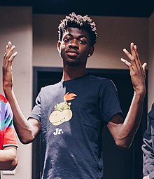 Lil Nas X with his hands upraised