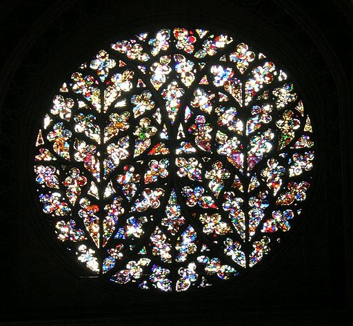 A round stained glass window with leaf-patterned tracery; the glass does not make a coherent image