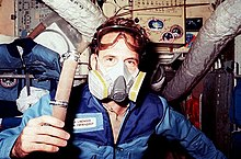 A man holding a piece of hose floats in front of a selection of transient space station hardware. He is wearing a gray-and-yellow plastic mask over his mouth and nose, a pair of goggles above his eyes, and a blue jumpsuit with a name patch on it.