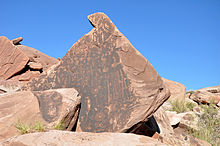 Images of animals, people, and geometric figures incised on the dark vertical face of a large rock