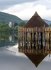 A small, brown conical structure sits on top of wooden piers set into a body of water. Ducks paddle through the water and in the near background there is a tree-lined shore with a white square tower showing amongst the trees. Tree covered hills and grey skies dominate the far background.