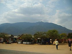 Shops on the main road running through Longido. Mount Longido can be seen behind, however the peak isn't visible from here.