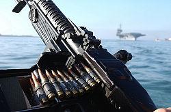 An M60 machine gun aboard a Navy patrol craft. The USS Constellation (CV-64) in the distance; July 2002