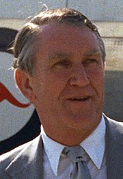 Colour photograph of a Malcolm Fraser aged about fifty, he has a weathered face and greying hair parted on the right. He wears a suit and tie; behind him can be seen part of a large aircraft with a kangaroo logo.