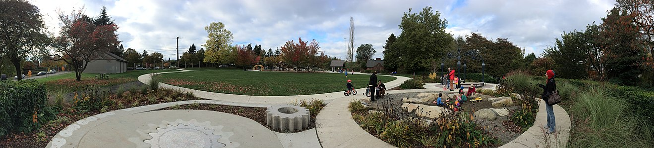 A busy park with children riding bikes, using playground equipment, and digging in a sandbox, with a blue water tower in the background.