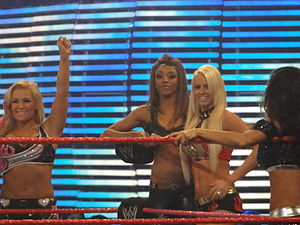An African American woman with straight dark-brown hair stands in the center of two blonde Caucasian women. All three women are wearing crop tops, and standing near to a corner turnbuckle on the apron of a wrestling ring with red ropes.