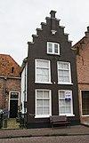 foto van woonhuis tussen gepleisterde trapgevels