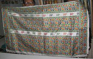 Mekhela chador - On display, a hand woven mekhela chador in pat silk depicting an exquisite pattern of wildlife in Kaziranga