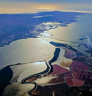 Mowry Slough - The Mowry Slough (lower center) where it meanders between salt ponds in the south San Francisco Bay, including the Don Edwards San Francisco Bay National Wildlife Refuge and the Dumbarton Bridge, with Peninsula cities in the background