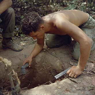 "A US ""tunnel rat"" soldier prepares to enter a Viet Cong tunnel. NARA 111-CCV-529-CC38112 Ronald A. Payne checking tunnel entrance Operation Cedar Falls 1967.jpg"