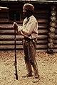 NPS employee dressed in historic clothing holding a gun in front of a log cabin. (11f2967ee96846e39bf2b8672d4e5fcb).jpg