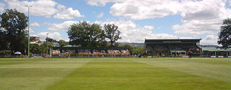 A cricket ground with two stands and several trees visible.