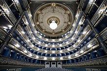 Vue depuis la scène des balcons d'un théâtre à l'italienne, puissamment éclairés. La tonalité de l'ensemble est bleutée.