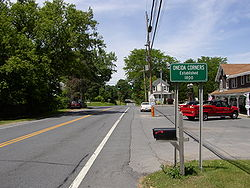 Sign along New York State Route 9L indicating Oneida Corners.