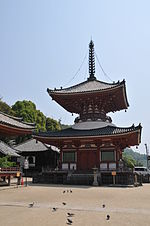 Wooden two-storied pagoda shaped building with a square base and a round upper floor, white walls and red beams.