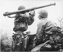 Two soldiers standing in brush, one aiming a bazooka