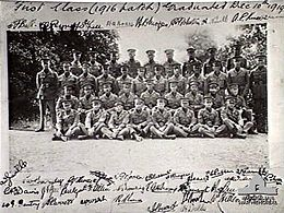 Group portrait of 38 men in military uniforms with peaked caps