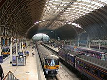 The interior of a large railway station with a curved roof supported by iron girders, supported by iron columns, four diesel trains standing at platforms, passengers on the platforms, in the distance daylight can be seen and the scene is illuminated by natural light through the centre section of the roof