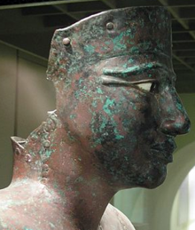 Closeup of the head of the statue of a man, made of greenish copper, its eyes inlaid in white and black stones