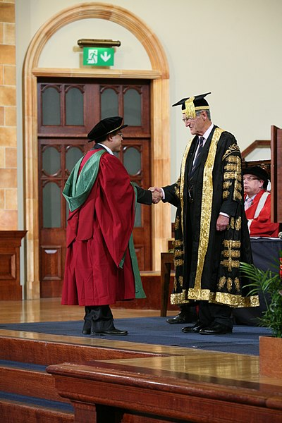 A new PhD graduate from the University of Birmingham, wearing a doctor's bonnet, shakes hands with the Chancellor PhD graduand shaking hands with Sir Dominic Cadbury, the Chancellor of the University of Birmingham - 20120705.jpg