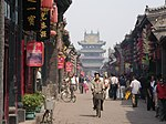 A street lined by traditional houses with red lampions leading to a multi-storied gate.