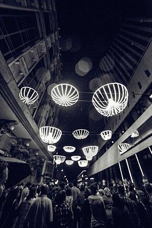 Le public est émerveillé par les street lights au festival Porlwi by light. La foule marche sur les rues illuminées de la capitale. L'image dégage un sentiment de fête et de joie.
