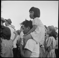 Poston, Arizona. A little evacuee of Japanese ancestry gets a ride on her father's shoulders. - NARA - 538555.tif