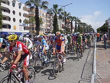 Dozens of professional bicyclists race on a street lined with palm trees and pastel apartments.