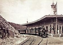 Fotografia de uma locomotiva a vapor e trem sentado em uma seção curva da pista ao lado de um edifício plataforma e estação de curva