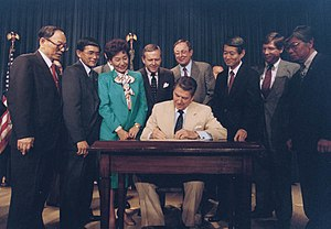 Japanese American redress and court cases - President Reagan signs the Civil Liberties Act into law. Looking on, left to right: Senator Spark Matsunaga, Representative Norman Mineta, Representative Patsy Sakai, Senator Pete Wilson, Representative Don Young, Representative Bob Matsui, Representative Bill Lowery, JACL President Harry Kajihara.
