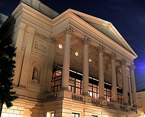 The photo shows the front of the Royal Opera House at night, illuminated from below