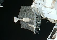 A rectangular dish shape of scaffolding covered in transparent sheeting, with a white insulation-covered radio receiver and support projecting from the centre. The blackness of space serves as the backdrop.