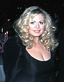 A standing woman with blond hair wearing a black dress looking directly at the camera and smiling.