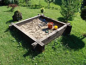 Sandpit with toy tools used by children to pla...