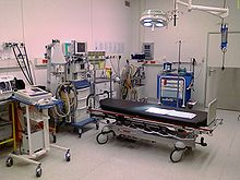 Color photograph of a room designed to handle major trauma. Visible are an anesthesia machine, a Doppler ultrasound device, a defibrillator, a suction device, a gurney, and several carts for storing surgical instruments and disposable supplies.
