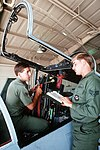 Senior Airman Tom W. Vessie attaches the cable of a Cobra crane to an ACESII ejection seat of an F-15C Eagle aircraft as Sgt. Mike W. Briery consults a manual to determine proper removal of the seat DF-ST-89-05902.jpg
