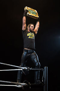 Seth Rollins holds Money in the Bank briefcase at a WWE house show in January 2015.jpg