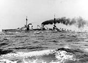 A large gray battlecruiser steams through choppy seas, thick black smoke pours from its rear smoke stack.