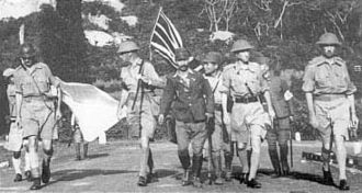 Khaki drill -  Lt Gen. Arthur Percival, led by a Japanese officer, walks under a flag of truce to negotiate the capitulation of Allied forces in Singapore, on February 15, 1942. All wear standard KD with shorts.