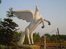 Sculptură modernă, albă, a unui cal mare cu aripi cu trăsături moi și puerile.