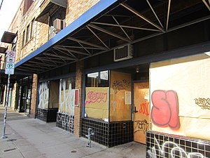 Photograph of the exterior of a two-story brick building with boarded windows and graffiti