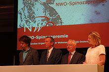 Four winners of the Spinoza Prize sit at a table on stage. They are all looking at a direction away from the camera