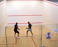 Players in a glass-backed squash court