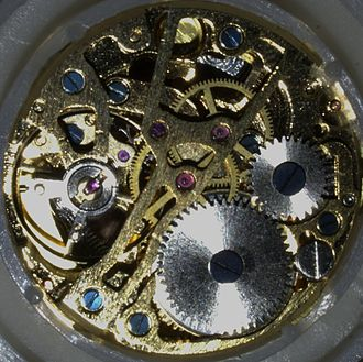 Chinese standard movement - A typical lower-quality skeletonized variant of the Chinese Standard Movement, frequently found today in cheap mechanical watches mass-produced and marketed by a large number of brand names. Note the rough finishing of the movement. The white plastic spacer ring designed to hold and stabilize the movement in its case is clearly visible around the movement. (photo 2008)