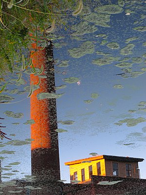 Flipped image - A flipped reflection in water of the Stanley Woolen Mill in Massachusetts
