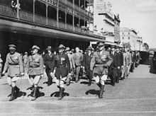 Black and white photo of a large group of middle-aged men marching in close formation down an urban street. The front rank of men are wearing military uniforms, and the remainder are wearing formal suits. Some of the men in suits have medals pinned on their coat lapel.