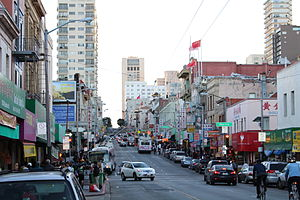 Stockton Street (San Francisco) - Stockton Street in Chinatown, seen from Broadway, with two Muni trolleybuses, and the mound of the Stockton tunnel in the far background.